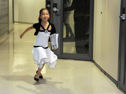 Kayla Bladzinski, 8 of Arnold, runs out of the room smiling after taking a music test of the new Achievement Program. The program is a venture by Carnegie Hall and Canada's Royal Conservatory of Music to establish nationally standardized testing of music skills.