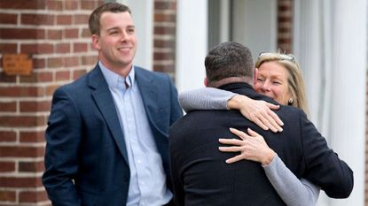Towson Chamber of Commerce president Tim Bojanowski, left, smiles while executive director Nancy Hafford gives former Howard County Executive Ken Ulman a hug during a Jan. 27 tour of Towson.