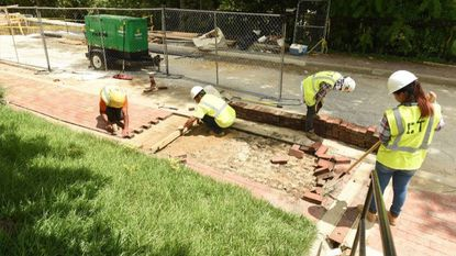 Workers make repairs to sidewalks damaged in the May 27 flood in downtown Ellicott City last month.