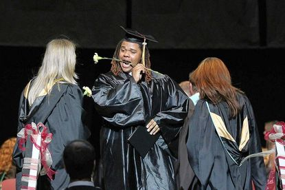 Kyle Jackson puts a flower in his mouth after receiving his diploma during Hammond High School's graduation ceremony May 29.
