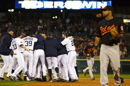Detroit designated hitter Victor Martinez is surrounded by his Tigers teammates after hitting a game-winning RBI single off Orioles reliever Zach Phillips in the 11th inning.