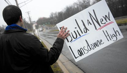 Lansdowne High School Magnet coordinator Luke Simon holds a sign up to passing cars on Hollins Ferry Road Feb. 23 during a rally asking for a new building.