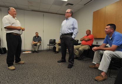 Wayne Koontz, left, and Mike Wilhelm, standing at right, both officers from Carroll County Community College, role-play a scene between an officer, played by Koontz, and a suicidal student, played by Wilhelm. Police from 9 Maryland college campuses participated in a training session held at Towson University to recognize mental illness and to be able to handle situations where this is a factor.