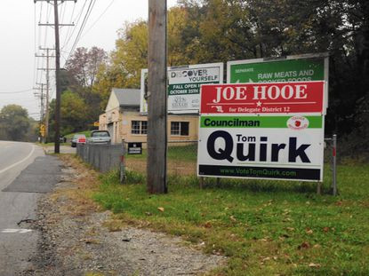 Democratic 1st District County Councilman Tom Quirk's sign is posted under a sign for Republican state delegate candidate Joe Hooe on Frederick Road in Oella.