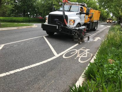 Baltimore Department of Public Works crews remove a protected bike lane on Roland Avenue. File.