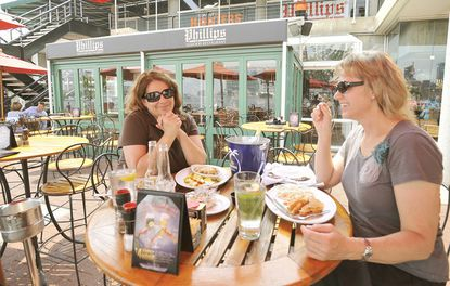 Debbie Page (left) and Tammy Novosad, both of Atlanta and Delta flight attendants, enjoy lunch at Phillips Seafood Restaurant at Light Street Pavilion in the Inner Harbor. Phillips Seafood will be closing its Inner Harbor location Sept. 30, ending more than three decades as an anchor of Harborplace's Light Street Pavilion.