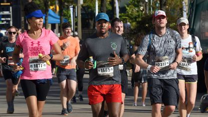 Runners reach the nine-mile mark on Light Street for the marathon last year. From left are Erica Harris (#1677), William Harris (#1685), Jacob Herritt (#2372) and Anna Thorson (#1832).