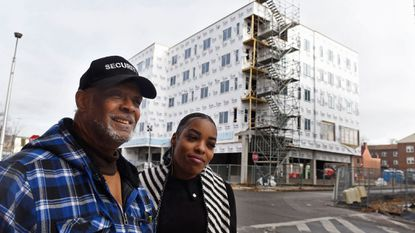 William Jackson and Ericka Flichman stand at the corner of West Lexington and North Schroeder streets. Behind them is Center West, an apartment building rising on once-vacant land It is the first new housing in Poppleton in many years.