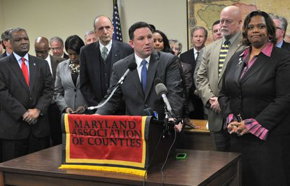 Howard County Executive Ken Ulman, at the microphones, and other leaders express concern about the governor's teacher pension plan.