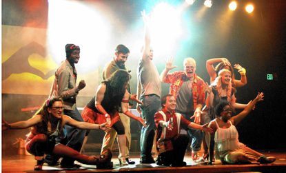 """The """"Godspell"""" cast at Silhouette Stages hits the finale of """"We Beseech Thee"""" with Jesus (Andrew Worthington) holding his arm in the air."""