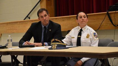 Baltimore County Executive Johnny Olszewski Jr. and new Baltimore County Police Chief Melissa Hyatt listen at a public safety town hall meeting in Randallstown on June 19.