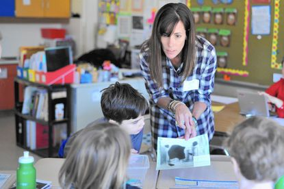 Leslie Wagner, a speech therapist at the Maryland School for the Blind, shows students, including fourth-grader Greg Zabora, an image showing what a person who is visually impaired might see during Appreciating Differences Day at Rodgers Forge Elementary School Feb. 10.