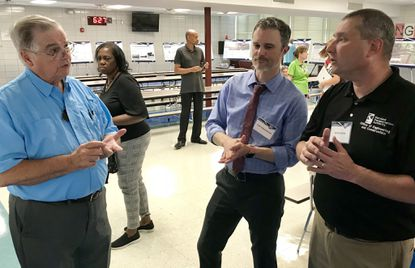 Joppa resident Adrian Cox, left, talks with Maryland Transportation Authority representatives Carl Chamberlin, a project manager, and Brian Wolfe, acting director of project development, during a public meeting Wednesday evening at William Paca/Old Post Road Elementary School, on extending Express Toll Lanes on I-95 north into Harford County.