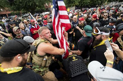 "Joseph Oakman and members of the Proud Boys plant a flag in Tom McCall Waterfront Park during an ""End Domestic Terrorism"" rally in Portland, Ore., on Aug. 17, 2019."