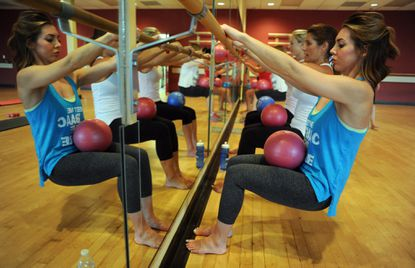 Kristyn Everson of Bel Air balances a ball in her lap along with other students during a barre exercise class at Bel Air Athletic Club.