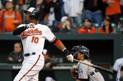 Baltimore Orioles' Adam Jones, left, doubles in front of Minnesota Twins catcher Kurt Suzuki in the fifth inning of an opening day baseball game in Baltimore, Monday, April 4, 2016. Manny Machado and Joey Rickard scored on the play.