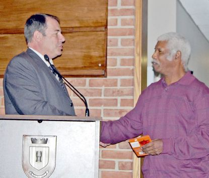 Jimmy Kennard, right, a longtime employee of the Town of Bel Air Public Works Department is congratulated on his retirement by Mayor Eddie Hopkins during Monday night's town meeting.