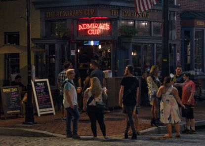 A group of people hang outside of Admiral's Cup in Fells Point. Baltimore's Atlas Restaurant Group is acquiring the dive bar.