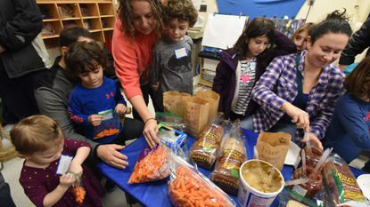 The Solomon family of Columbia, from left, Lyla, 2, Max, 4, and Jordan, 6, pack lunches with help from parents, John and Judy. Ilyse Reid of Columbia, right, make sandwiches with assistance from her nieces, 8-year-old twins Shannon, front, and Mira.