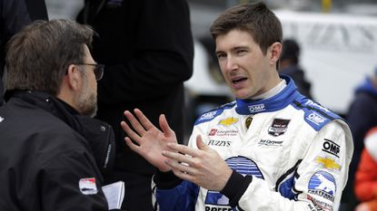 IndyCar Series driver J.R. Hildebrand, right, speaks with a member of his crew after an Indianapolis 500 practice session on May 15. Hildebrand is eager to prove he can win the Indianapolis 500 after his heartbreaking, final-lap loss in 2011.