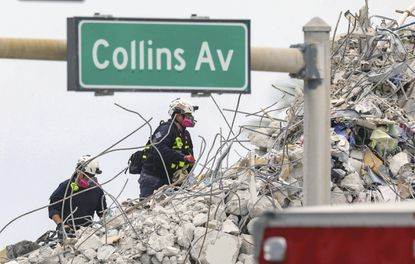 Search and rescue team members climb the debris field of the 12-story oceanfront condo, Champlain Towers South along Collins Avenue in Surfside, Florida on Wednesday, July 7, 2021. (Al Diaz/Miami Herald via AP)