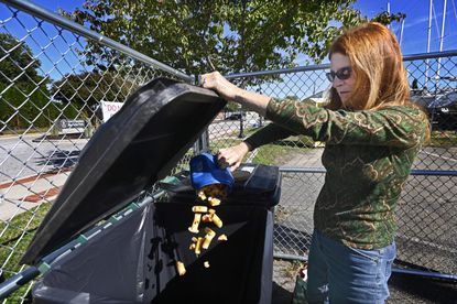 Trisha Tatam-McQuate, of Havre de Grace, deposits a food waste into collecting bins at the city's new compost center twice a week. About 700 pounds of food waste a week are collected from residents to be recycle into compost.