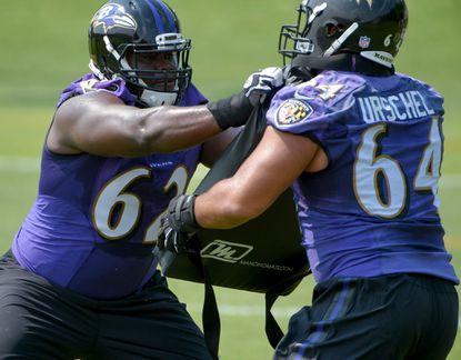 Baltimore Ravens guard Vladimir Ducasse (62) hits offensive lineman John Urschel (64) during minicamp at the Ravens' training facility.