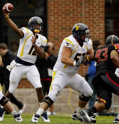 West Virginia quarterback Geno Smith, left, throws to a receiver as he is protected by offensive lineman Jeff Braun Sept. 17, 2011, in College Park.