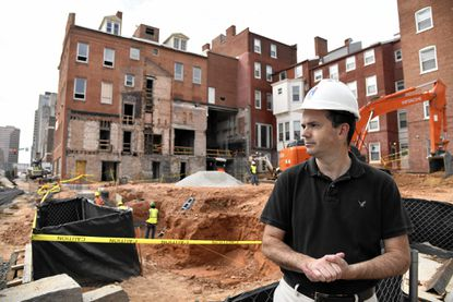 James M. Riggs, vice president of Osprey Property Companies, stands with the site of 20 E. Franklin Street behind him. His company is developing the existing building and some new construction into 40 apartments.