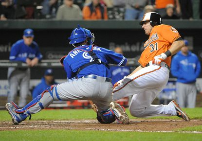 Taylor Teagarden is tagged out at home by Toronto catcher J.P. Arencibia as he tried to score on a Chris Davis fly to left in the sixth inning of Monday's nightcap.