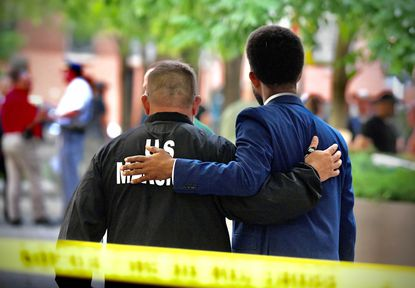 Walking outside Shock Trauma, Baltimore Mayor Brandon Scott extends his arm around Don Snider with the U. S. Marshals. Two officers with the multi-jurisdictional Warrant Apprehension Task Force were shot while attempting to serve a warrant on a 32-year-old man, who has not yet been identified, for a homicide that occurred on West Lanvale Street in Baltimore on June 19. (Karl Merton Ferron/Baltimore Sun)