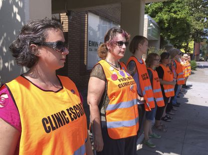 In this July 17, 2017 file photo, escort volunteers line up outside the EMW Women's Surgical Center in Louisville, Ky., the state's only abortion clinic. (AP Photo/Dylan Lovan, File)