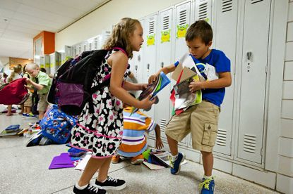 Carlye Rubenstein, 7, helps her classmate Nathan Ross, also 7, gather his belongings off of the floor on their first day of second grade at Relay Elementary School on Aug. 26.