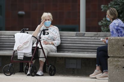 A resident sits socially distant outside the Jack Satter House, Wednesday, June 3, 2020, in Revere, Mass. Massachusetts residents with family members in nursing homes and some other long-term care facilities began visiting their loved ones again on Wednesday under new state guidelines meant to slow the spread of the coronavirus. (AP Photo/Elise Amendola)