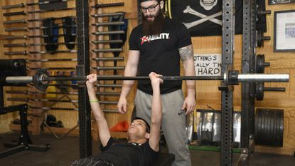 Miles Taylor works out on the bench as part of his routine with coach Nicolai Meyers. Taylor, a 2013 Westminster graduate with cerebral palsy, weighs just 99 pounds. He gained widespread social media attention when a video of him deadlifting 200 pounds went viral.