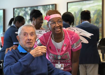 Dawn Washington, a 12-year employee of Charlestown Retirement Community, with resident Robert White at an event campus.