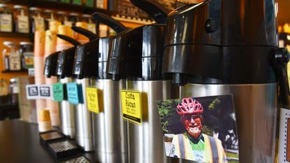 """Tom's Trailblazer Blend, in the thermos on the right, has a photo of the late Tom Caraker on it. The Big Bean coffee shop in Severna Park has a new coffee blend named after Caraker, who was known as """"mayor"""" of the B&A trail."""