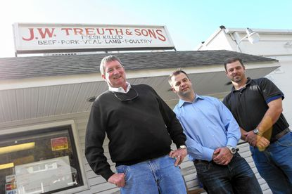 Michael Treuth, left, the previous owner of J.W. Treuth & Sons, stands with new owners Jason Trippett, of Severna Park, and Mike Trippet, of Hagerstown at the meat packing company in Oella.