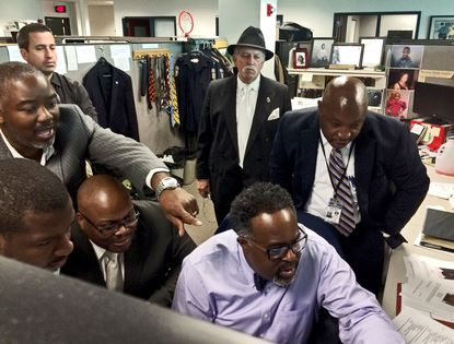Homicide detectives crowd around the desk of Det. Damon Talley as he pores over surveillance footage of the Sept. 21, 2015 fatal shooting of Kevin Cannady, 29. The conviction and life sentence of the man charged with killing Cannady was overturned this week by a Maryland appeals court.