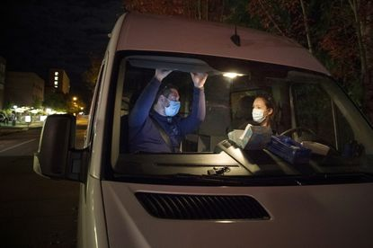 In this Oct. 2020 photo, Emergency Medical Technicians Henry Cakebread, left, and Ashley Barnhill-Hubbard with CAHOOTS, a mental health crisis intervention program, discuss their last encounter during their night shift in Eugene, Ore. When police respond to a person gripped by a mental health or drug crisis, the encounter can have tragic results. Now a government health program will help communities set up an alternative: mobile teams of practitioners trained in de-escalating such potentially volatile situations. (William Holderfield via AP)