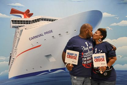 Philip and Miracarla Jackson of Philadelphia, who are celebrating their first wedding anniversary, pose for a Carnival Cruise Line photographer before boarding the ship.