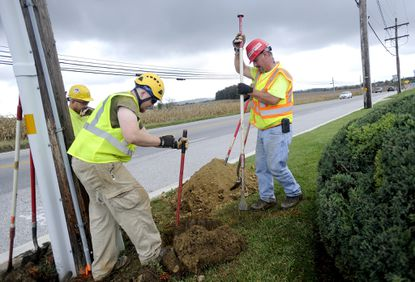 Merle Barton, right, and Bryan Higgins, center, dig holes to look for existing utility lines in preparation for the laying of fiber optic lines along Md. 97 in Westminster Oct. 16.