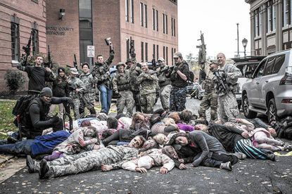 Extras portraying soldiers in the movie 'My Boring Zombie Apocalypse' stand over a pile of extras playing dead zombies during a shooting of a scene on Office Street in Bel Air Saturday.