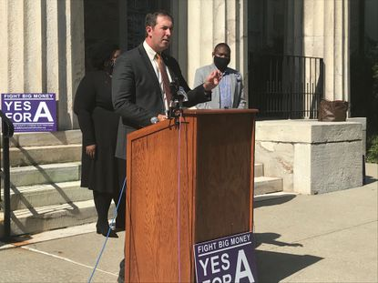 """Baltimore County Executive Johnny Olszewski Jr. speaks Tuesday at an event launching the """"Yes for A!"""" campaign, which urges voters to approve a ballot measure that would allow public financing for local political campaigns."""