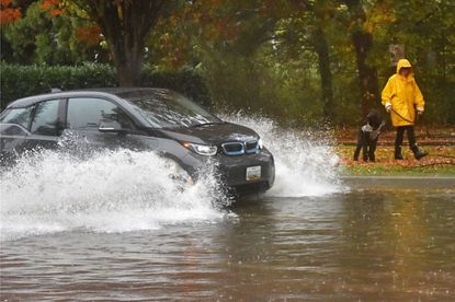 Jennie Boyd of Roland Park, walking her dog, Eli, watches cars plow through standing water on Roland Avenue at the intersection of Gladstone Avenue. Oct. 27, 2019