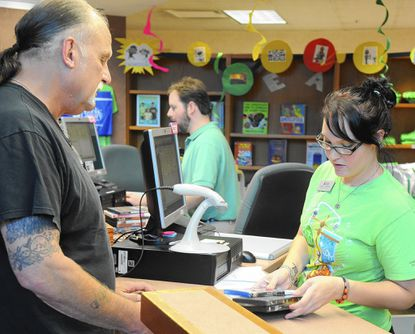 Library employee Caitlin Vogtman helps patron Jeffrey Brock check out his items Monday afternoon at the Bel Air Branch of the Harford County Public Library.