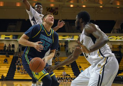 Towson Tigers guard Mike Morsell watches forward Arnaud William Adala Moto (right) slap the ball from UNC Wilmington Seahawks center C.J. Gettys (23) as he fails to power to the basket during an early CAA matchup at Towson University.