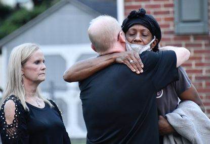 An unidentified neighbor, right, hugs homeowner Mark Flenner as a relative looks on at left. Flenner came home from work after firefighters had the one-alarm fire under control. Flenner said his younger brother, Kurt Flenner, 54, was taken to Bayview after firefighters rescued him from his basement apartment.