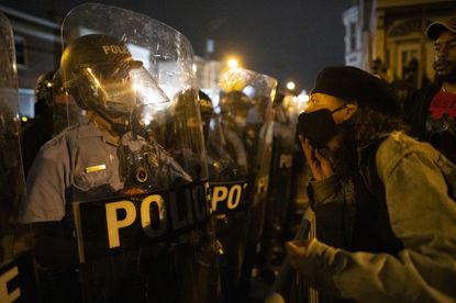 A demonstrator confronts police officers forming a barricade line during a protest near the location where Walter Wallace Jr. was killed by two police officers Oct. 26, 2020, in Philadelphia.