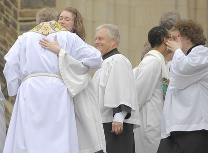 People embrace on the front steps, following a Eucharist of the Resurrection of Rev. Dr. Mary-Marguerite Kohn at The Cathedral of the Incarnation.